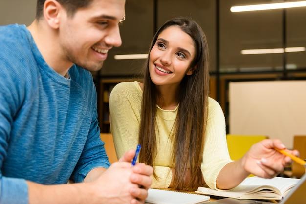 Foto di una coppia di amici di due giovani studenti in biblioteca a fare i compiti studiando leggere e utilizzando il computer portatile.