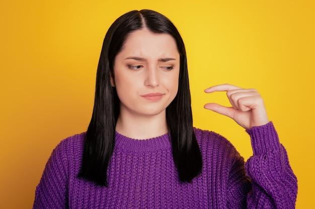 La foto di una donna insoddisfatta e indifferente misura il segno delle dita dimostra qualcosa di poco isolato su uno sfondo di colore yellov
