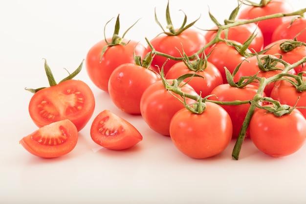 Foto di pomodori molto freschi presentati su sfondo bianco