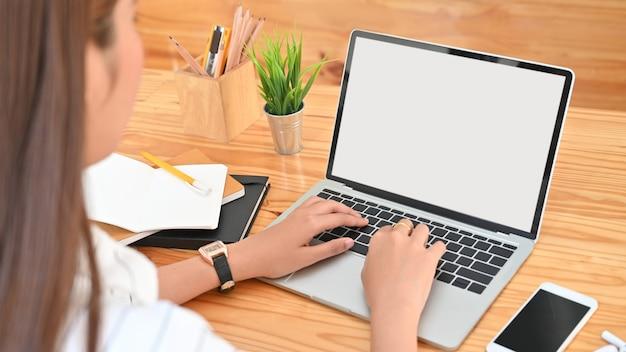 Viste della foto dalla parte posteriore della giovane donna mentre si utilizza / si digita sul computer portatile bianco schermo vuoto incluso portamatite, smartphone schermo nero bianco, pianta in vaso, matita, note, auricolare sulla scrivania in legno.