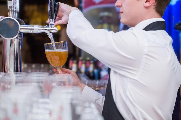 La foto del cameriere versa la birra in un bicchiere