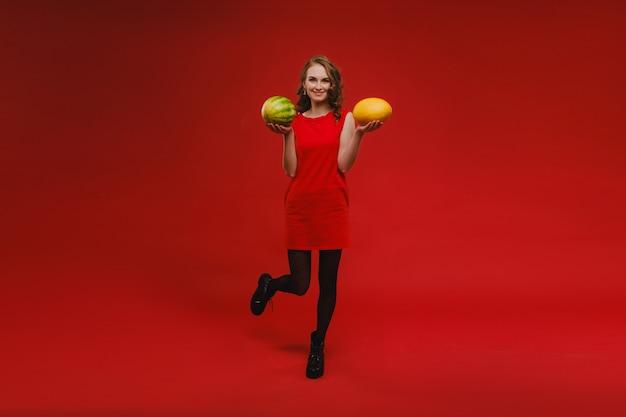 Foto della ragazza carina positiva allegra ondulata sorridente e con meloni isolati sopra la parete rossa vivida