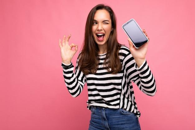 Foto di una bella giovane donna felice che indossa un maglione a righe isolato su sfondo con