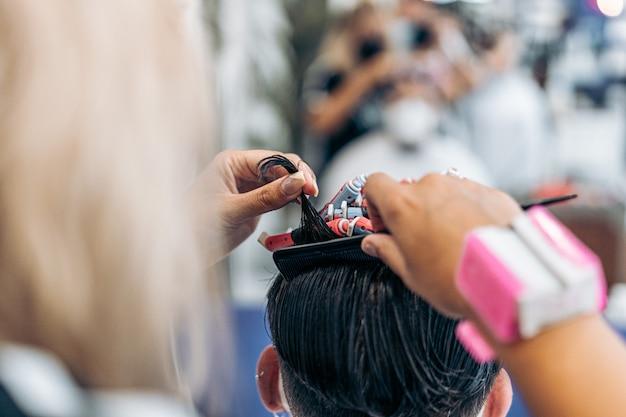 Foto con copia spazio di un parrucchiere che usa un pettine per arricciare i capelli di un uomo caucasico in un salone