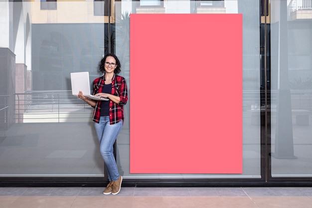 Foto con copia spazio di una commessa di fronte alla telecamera con un laptop accanto a una vetrina all'aperto