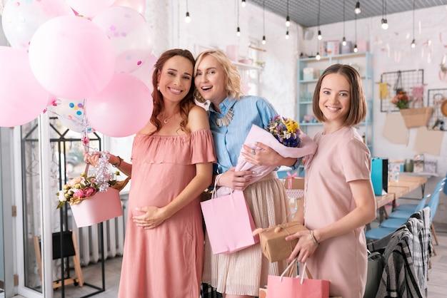 Foto con sorelle. donna incinta sorridente che si sente adorabile mentre fa la foto memorabile con le sue sorelle