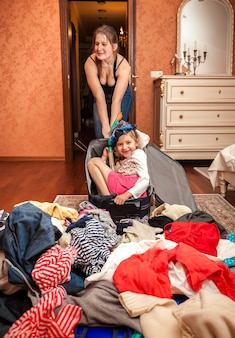 Foto di una donna che porta una grande valigia con una ragazza seduta dentro