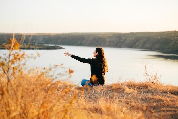 Foto di donna seduta su una collina vicino al fiume durante il tramonto e che punta da qualche parte