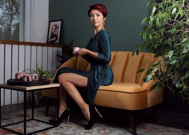 Foto di una donna con un elegante abito da sera e un'acconciatura luminosa con una tazza di caffè caldo