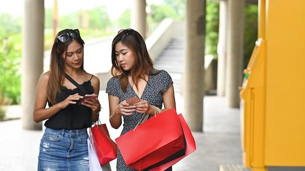 Foto delle donne che tengono le borse rosse e il telefono in mano mentre parlano e camminano insieme dopo aver finito di fare shopping al supermercato urbano con all'aperto soleggiato e bancomat giallo