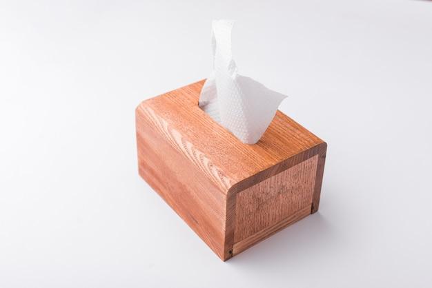 Foto della scatola di legno con tovaglioli sul tavolo bianco
