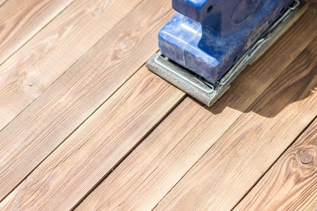 Foto del pavimento in legno e della smerigliatrice blu