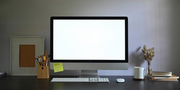 Foto del monitor del computer dello schermo in bianco dell'area di lavoro che mette sullo scrittorio funzionante e circondato dalla cornice, dal portamatite, dalla pila di libri, dal topo senza fili, dalla tastiera, dalla tazza di caffè e dall'erba selvatica in vaso.