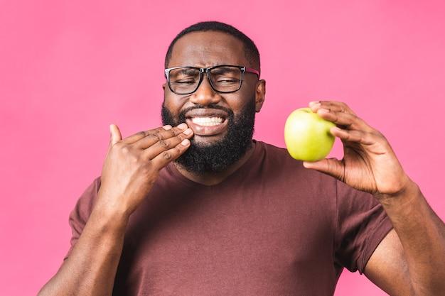 Foto di un giovane uomo di colore afroamericano isolato su sfondo rosa che soffre di un terribile dolore ai denti, mostrandolo vividamente sul viso, con un aspetto turbato e angosciato.