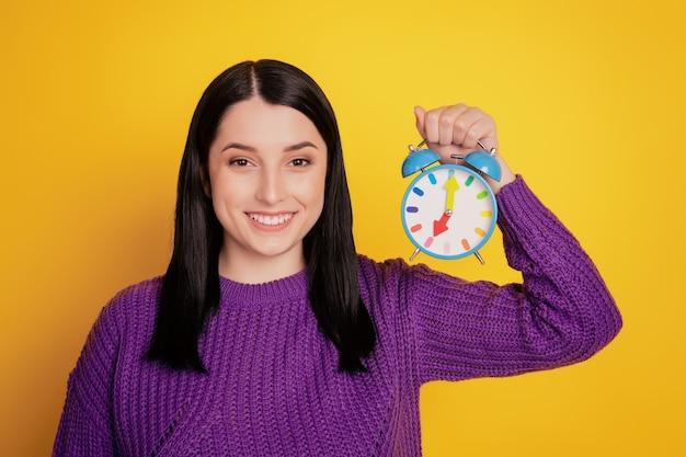 Foto di una giovane ragazza attraente felice sorriso positivo tenere la sveglia dell'orologio isolata su uno sfondo di colore giallo