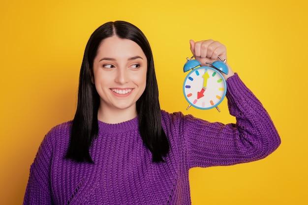 Foto di una giovane ragazza attraente felice sorriso positivo guarda la scadenza del timer della sveglia isolata su uno sfondo di colore giallo
