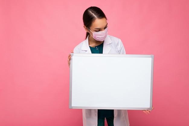 Foto di una giovane infermiera attraente con una maschera protettiva che tiene in mano una lavagna magnetica vuota con spazio per le copie per informazioni isolate su sfondo rosa.