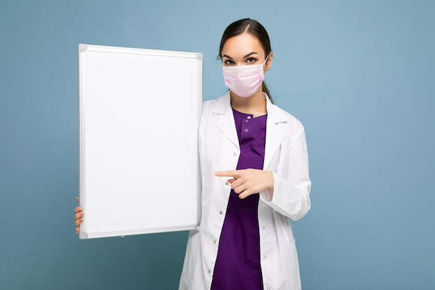 Foto di giovane infermiera attraente in maschera protettiva e camice medico bianco che tiene una lavagna magnetica vuota isolata sull'azzurro.