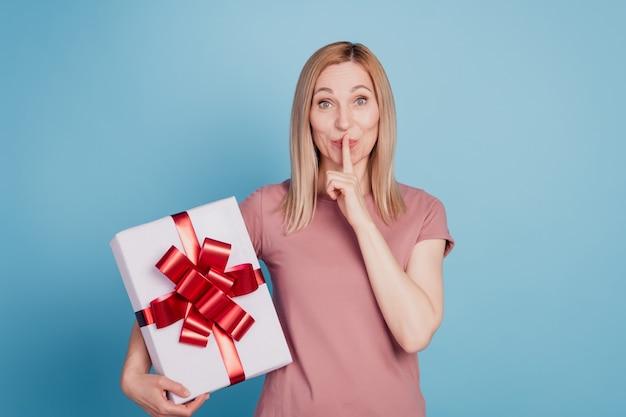 Foto di una giovane donna attraente che copre le labbra del dito shh sorpresa presente scatola celebrazione isolato sfondo di colore blu