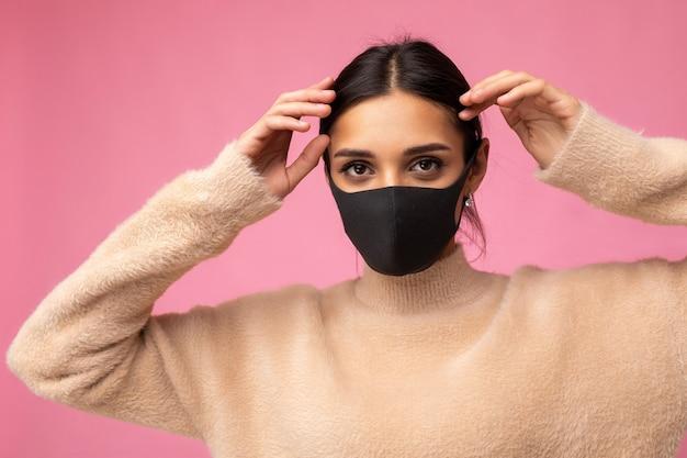 Foto di una giovane donna attraente che indossa una maschera facciale in tessuto di cotone fatta a mano isolata su una parete di fondo colorata. protezione contro il covid-19.
