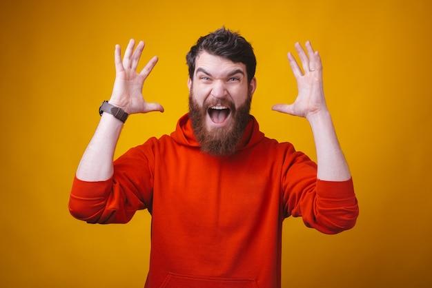 La foto di un giovane uomo barbuto arrabbiato sta gridando alla telecamera su spazio giallo.