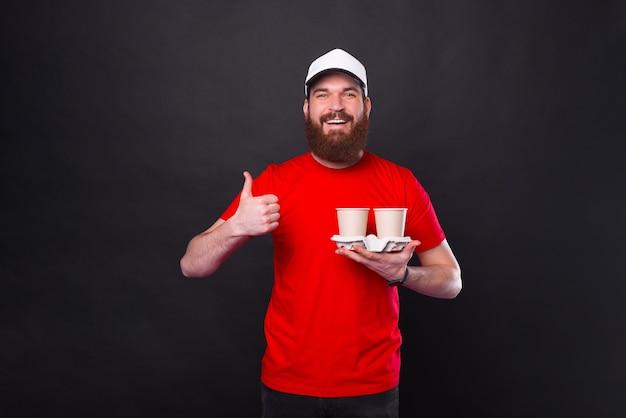 Foto di giovane uomo barbuto hipster in maglietta rossa che tiene due tazze di caffè e che mostra il pollice in su