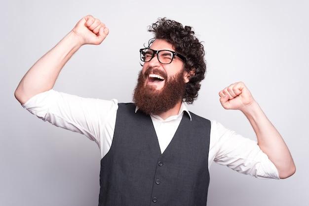 Foto di giovane uomo barbuto in vestito che indossa occhiali da vista e celebra la vittoria