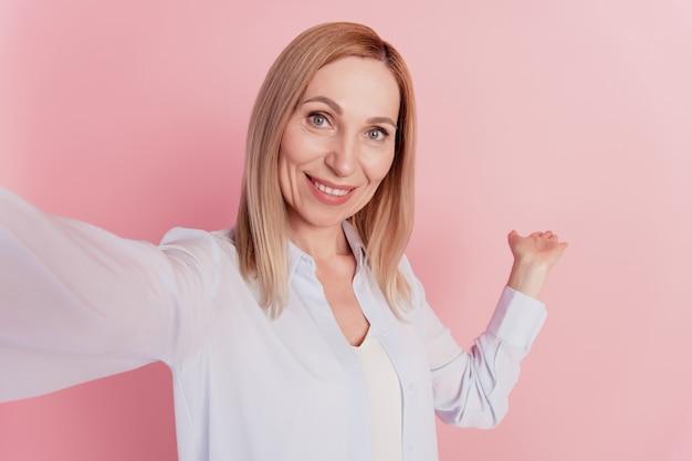 La foto di una giovane e bella ragazza sorridente allegra e positiva dimostra di prendere un selfie isolato su uno sfondo di colore rosa