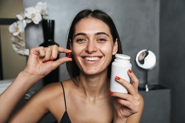 Foto di giovane bella donna in bagno che tiene le pillole di vitamine nelle mani.