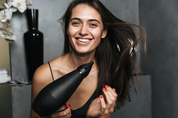 Foto di giovane bella donna in bagno prendersi cura dei suoi capelli con l'asciugatrice.