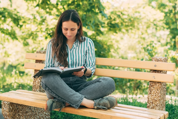 Foto di una giovane bella donna seduta su una panca di legno nel parco e che scrive in agenda o pianificatore