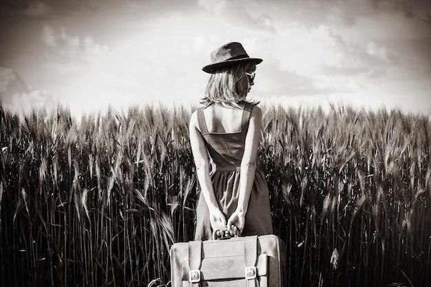 Foto di giovane bella donna con la valigia nel campo. immagine in stile colore bianco e nero