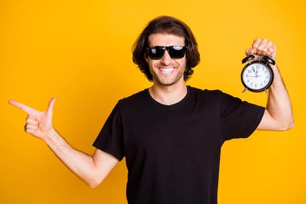 La foto del giovane uomo con le setole indica lo spazio vuoto del dito diretto tenere la sveglia mostra l'ora t-shirt occhiali da sole isolato sfondo di colore giallo