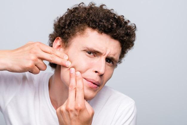 Foto di giovane uomo brunet alla ricerca di acnes sul suo volto isolato su grigio chiaro