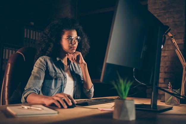 La foto della giovane signora di affari guarda il monitor del grande schermo che lavora fuori orario