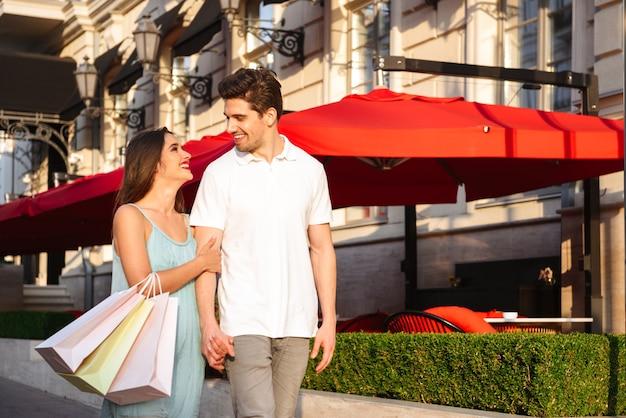 Foto di giovani coppie amorose sveglie che camminano all'aperto mentre tengono le borse della spesa