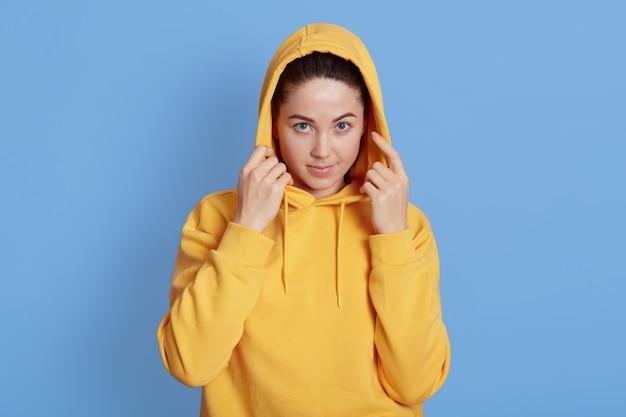 Foto di una giovane donna dai capelli scuri con trucco naturale che tiene le mani sul suo cappuccio mentre guarda attentamente la telecamera, in piedi su sfondo blu, abiti con cappuccio giallo.