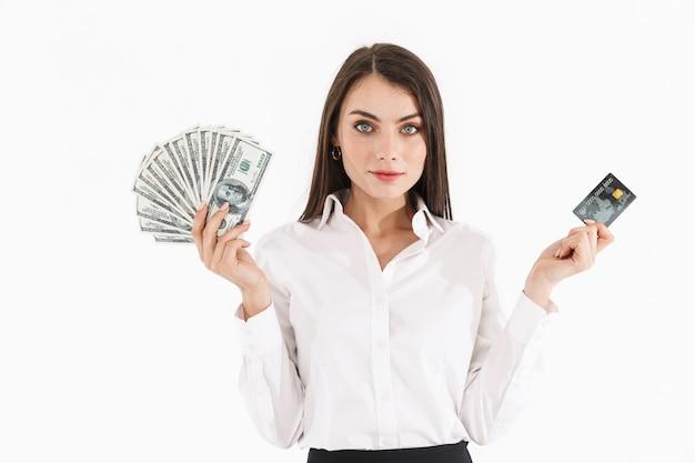 Foto di una giovane donna d'affari lavoratrice vestita con abiti formali che tiene denaro contante e carta di credito mentre lavora in ufficio isolato su un muro bianco