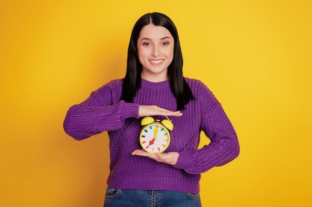 Foto di una giovane ragazza felice sorriso positivo tenere la sveglia dell'orologio isolata su uno sfondo di colore giallo