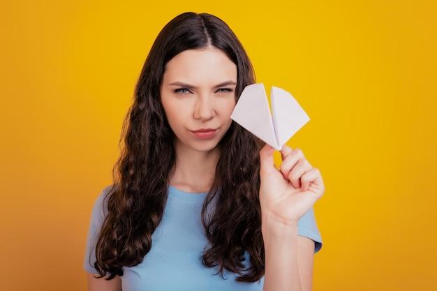 Foto di una giovane ragazza che lancia lo spazio vuoto di un aereo origami indossando occhiali isolati con sfondo di colore giallo