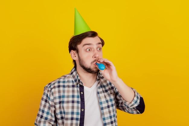 Foto di giovane ragazzo che soffia palloncino indossa carta cono cappello festa di compleanno celebrazione isolato colore giallo sfondo