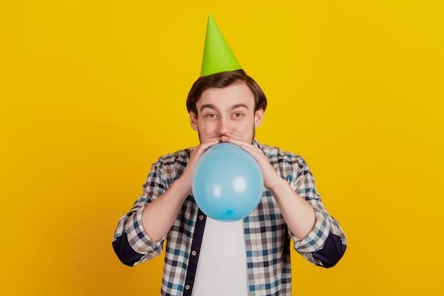 Foto di un giovane ragazzo che soffia un palloncino indossa un cappello a cono di carta decorazione della festa di compleanno isolato sfondo di colore giallo