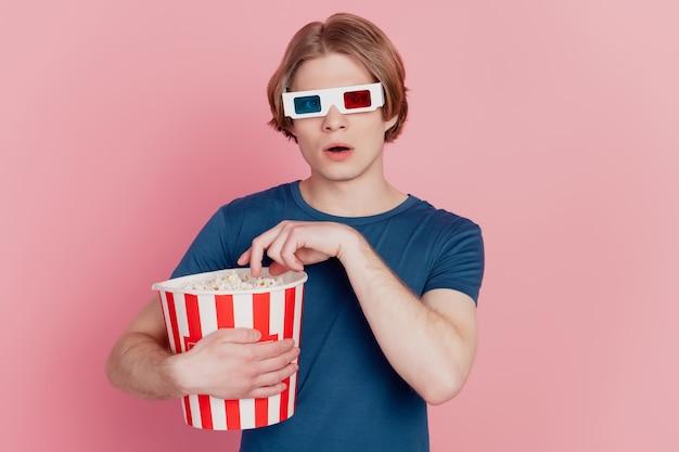 Foto di un giovane che tiene in mano una scatola di carta per popcorn indossa occhiali 3d e guarda un film isolato sfondo di colore rosa
