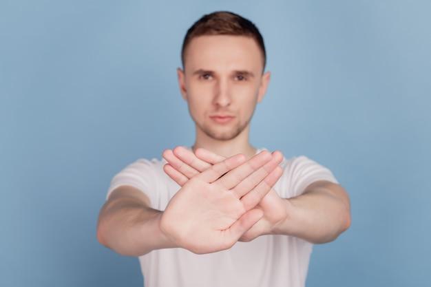 La foto di un giovane bell'uomo infelice con le palme incrociate ferma il divieto di blocco del declino isolato su uno sfondo di colore blu