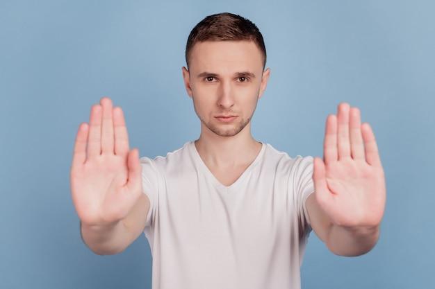 La foto del giovane uomo bello infelice triste mostra nessun segnale di stop abbastanza nega le regole isolate su uno sfondo di colore blu