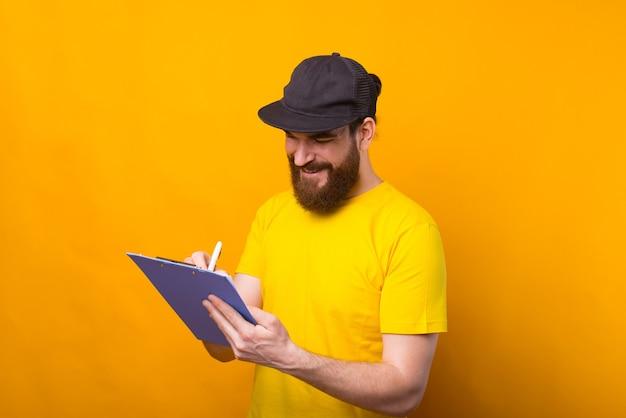 Foto di giovane uomo felice che prende appunti sul foglio di carta