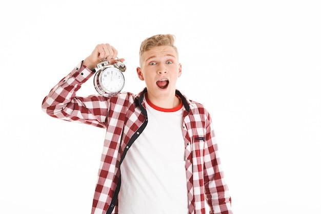 Foto di giovane uomo di 16 anni hipster in sveglia casuale della tenuta e che esprime emotivamente tempo tardivo, isolato sopra la parete bianca