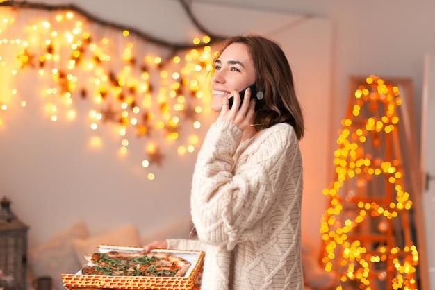 La foto di una giovane donna ordina una pizza mentre parla al telefono.