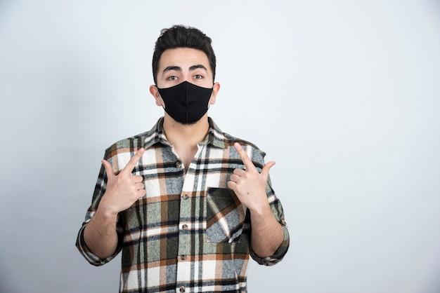 Foto di giovane uomo con maschera nera per protezione coronavirus in piedi sopra il muro bianco.