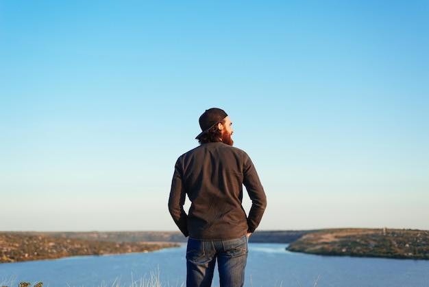 Una foto di un giovane da dietro in piedi vicino a un fiume